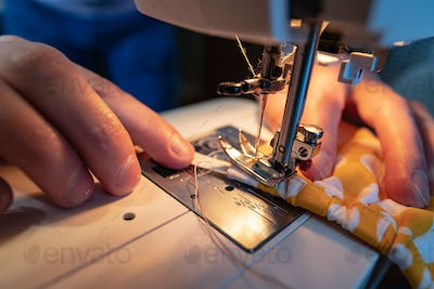 Hands sew protective mask using electric sewing machine. Concept of safety during viral epidemic