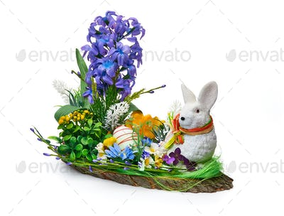 Easter installation from a flower arrangement and a rabbit on a white background