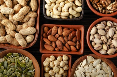 Flat lay view at assorted nuts and seeds in clay bowls on wooden kitchen table