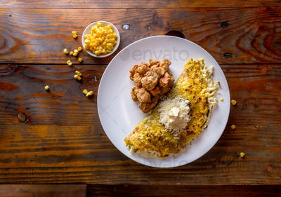 VENEZUELAN FOOD. Corn CACHAPA with cheese and fried pork - cochino frito. Wooden background, top