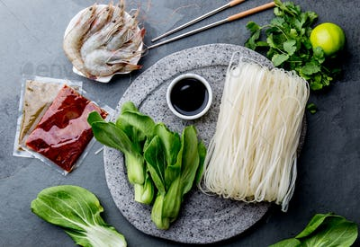 Asian cooking ingredients: rice noodles, pok choy, sauces, raw shrimps. Asian food concept Chinese