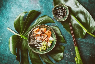 Hawaiian salmon poke poce with avocado, rice and sesamo served in bowls on tropical leaves. Sushi