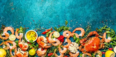 Baner. Fresh raw seafood - shrimps and crabs with herbs and spices on turquoise background. Copy