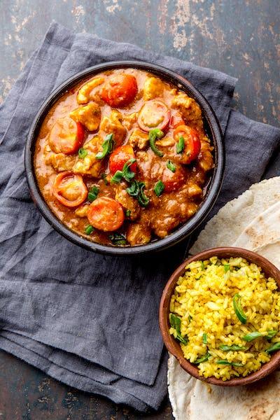 INDIAN FOOD. ROGAN JOSH curry sauce. Pork rogan josh with rice and naan bread