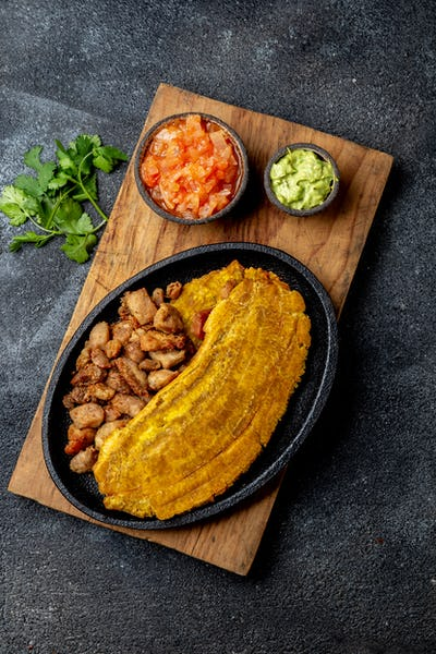 CARIBBEAN CENTRAL AMERICAN FOOD. Patacon or toston, fried and flattened whole green plantain