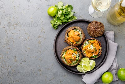 Caviar of sea urchins with onion, cilantro and lemon inside of shell of sea urchins.