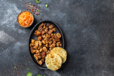 COLOMBIAN FOOD. Fried pork CHICHARRON, AREPAS and colombian tomato sauce. Top view. Black background