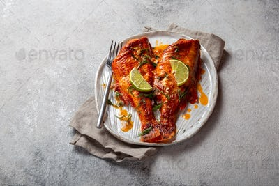 Baked red sea bass on kraft white plate, concrete background.