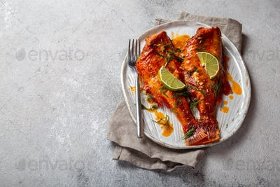 Baked red sea bass on kraft white plate, concrete background