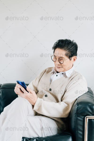 Portrait of senior man video chatting with smartphone at home