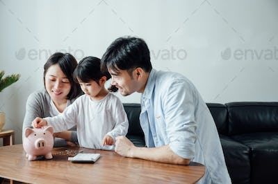 Parents teaching daughter to save money at home