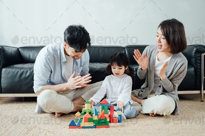 Happy family playing with building blocks at home