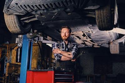 Mechanic holds nut key under the car.