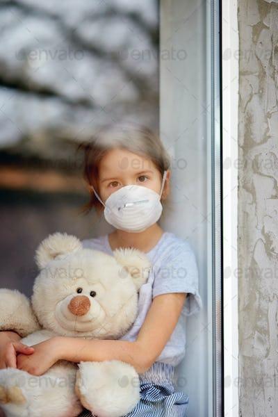 Sad Child, little girl in mask with teddy bear looking from window, coronavirus quarantine