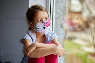 Little girl, child in mask sits on windows, coronavirus quarantine