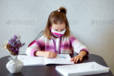 Schoolgirl girl in mask studying homework at home, social distance during quarantine coronavirus