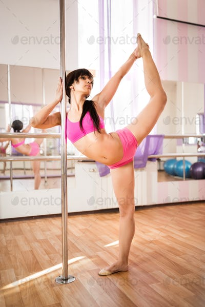 Young brunette woman standing near pylon in dance studio and stretching her legs