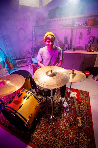 Cheerful young man sitting by drumset in his garage and going to have rehearsal