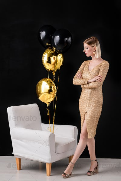 Girl in golden color dress and high-heeled shoes looking at bunch of balloons