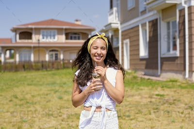 Happy young woman with dark long hair standing against green lawn and new house