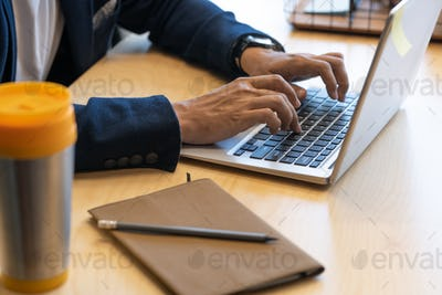 Hands of young contemporary office manager pressing keys of laptop keypad