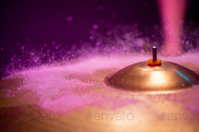Tiny waterdrops hitting cymbal of golden color against purple background