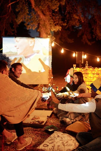 Young cheerful football fans clinking with beer in front of large white screen