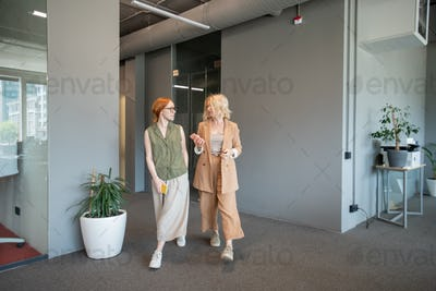 Mature blond businesswoman and her young red haired colleague with smartphones