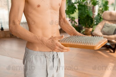 Shirtless sportsman with massage yoga pad going to practice meditation exercises