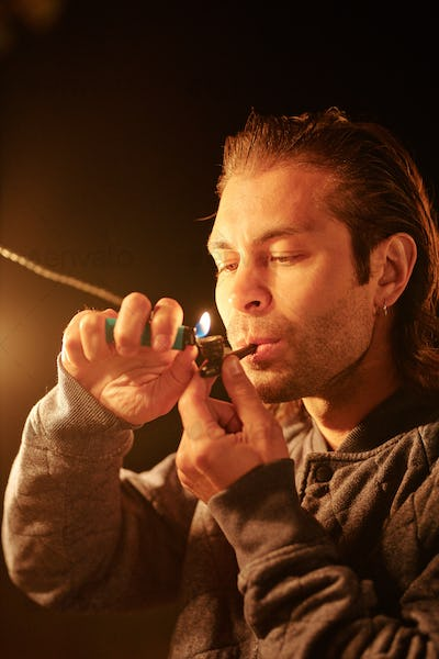 Young casual man with tobacco pipe in mouth holding lighter over its wide part