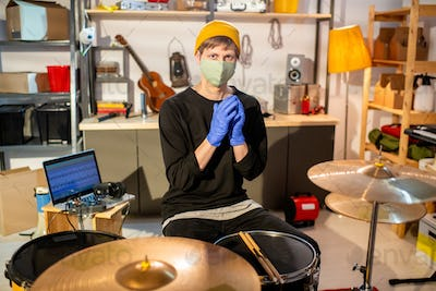 Contemporary musician in protective gloves and mask sitting in front of drumset