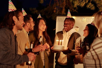 Young African man with birthday cake looking at his friends toasting with drinks