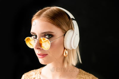 Young blond glamorous woman in white headphones and stylish sunglasses
