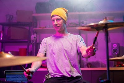 Contemporary young musician in casualwear touching cymbals with drumsticks