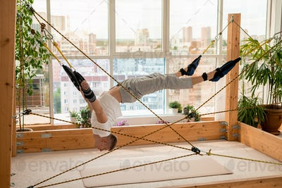 Young sportsman with his arms and legs fixed to ropes doing aerial yoga exercise