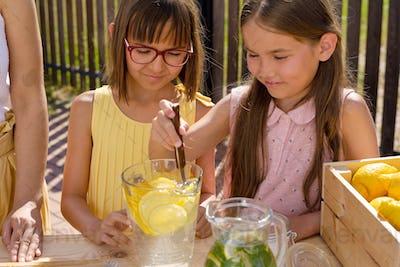 Two little pretty girls helping their mom make fresh lemonade for sale