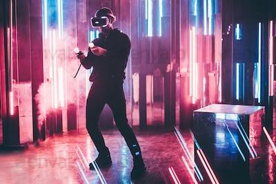Man using VR headset in dark interior illuminated neon light.