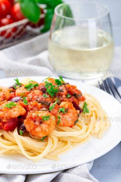 Italian dish shrimp linguine Puttanesca, pasta with shrimps in spicy tomato basil sauce vertical