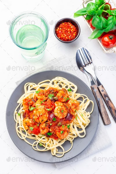 Linguine Puttanesca pasta with shrimps in spicy tomato basil sauce, vertical, top view