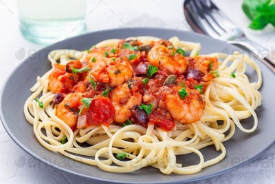 Linguine Puttanesca pasta with shrimps in spicy tomato basil sauce, horizontal