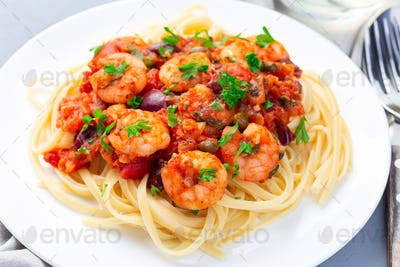 Italian dish shrimp linguine Puttanesca, pasta with shrimps in spicy tomato basil sauce, horizontal
