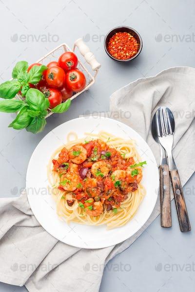 Italian shrimp linguine Puttanesca, pasta with shrimps in tomato basil sauce vertical, top view