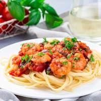 Italian linguine Puttanesca, pasta with shrimps in tomato basil sauce horizontal