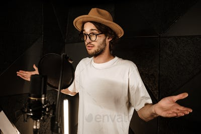 Young amazed male singer keep hands aside while recording song in modern studio. Doubt expression