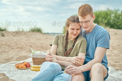 Young couple enjoying picnic on beach embracing and holding cups
