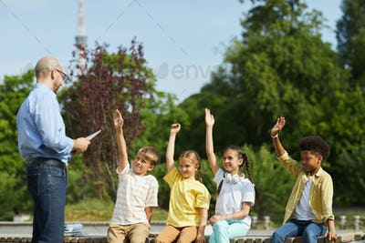 Group of Kids Raising Hands in Outdoor Lesson