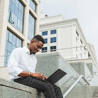 Handsome young businessman working with laptop outdoors at business building