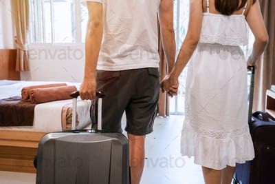 Young happy couple traveler with luggage at the hotel room on summer vacation