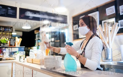 Young woman with face mask working indoors in cafe, disinfecting counter