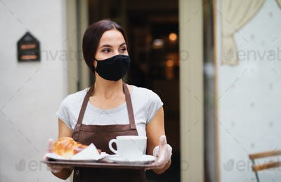 Waitress with face mask working in cafe, serving customers
